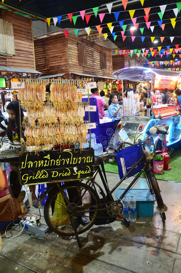 Thai people sell grilled dried squid in temple carnival retro. At IMPACT Muang Thong Thani on October 16, 2015 in Nonthaburi, Thailand royalty free stock photo