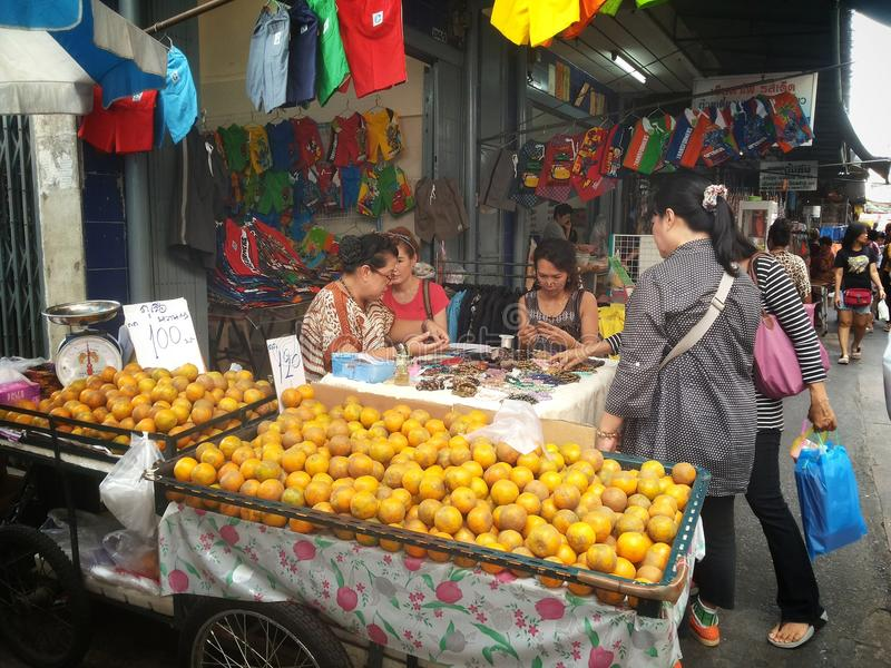 Thai people shopping for fruits and bracelet at the market. Bangkok Thailand stock photography