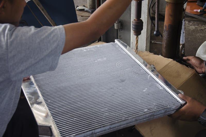 Thai people use drill machine drilled radiator of car. At local garage at Nonthaburi, Thailand royalty free stock photo