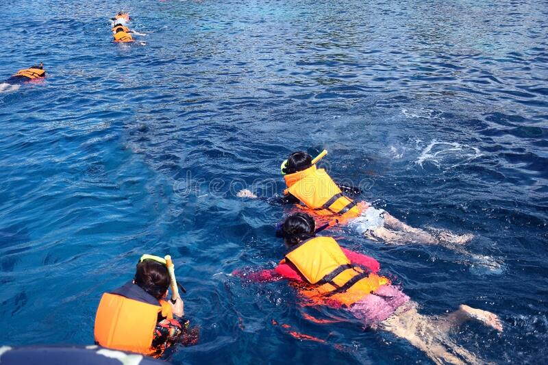 Thai photo of people snorkeling in tropical waters in Chang island Thailand. Scuba diving, snorkeling and see the fish.Diving,. Swimming, watching the fish in stock photo