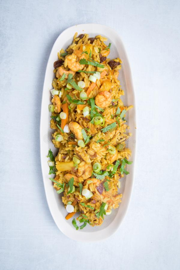 Thai Pineapple Fried Rice. Meal served on a white plate with a white background. Homemade gourmet Thai rice dish with vegetables, prawns and herbs stock photo