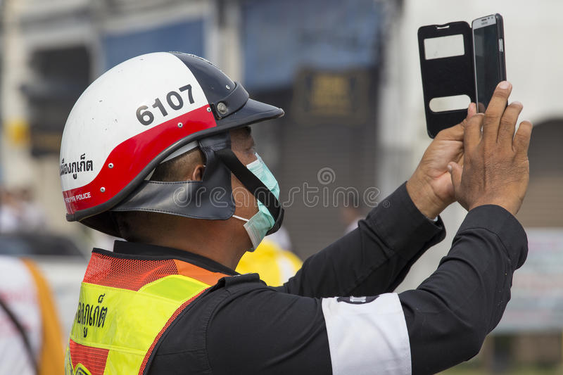 Thai police photographs on the smartphone procession during the Vegetarian Festival at Phuket Town. Thailand royalty free stock image