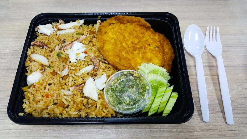 Thai ready meals that is crab fried rice food in ihe black plastic bento box on the wooden table with fork and spoon stock photo