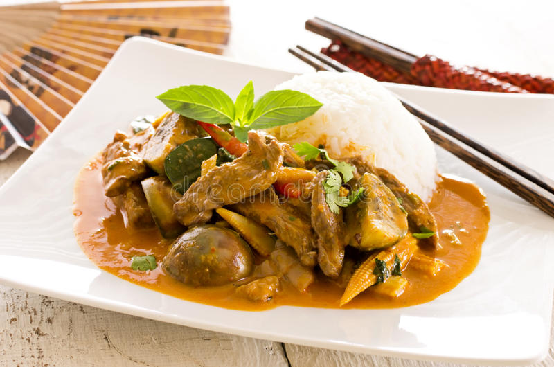 Thai Red Curry with Rice. As closeup on a white plate stock images