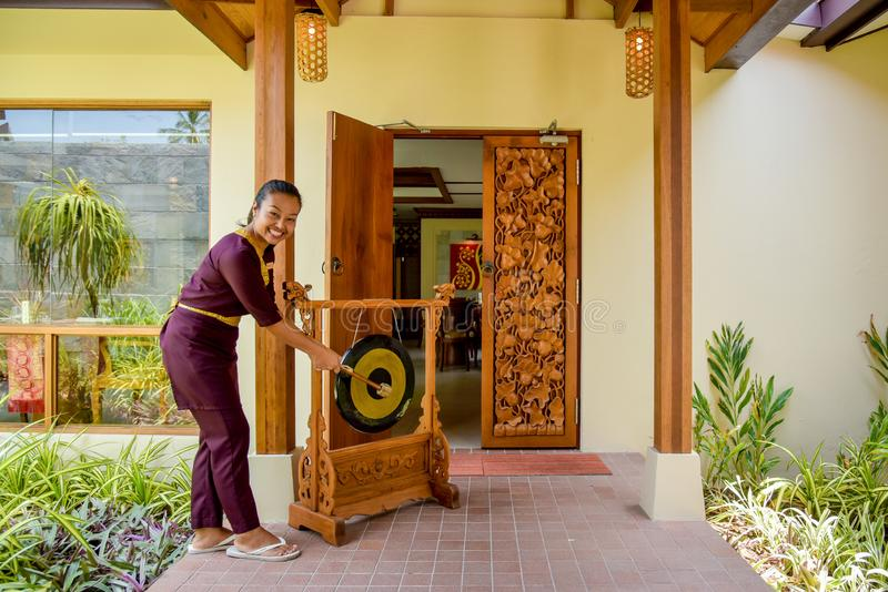 Thai restaurant waitress hitting the gong and smiling royalty free stock photos