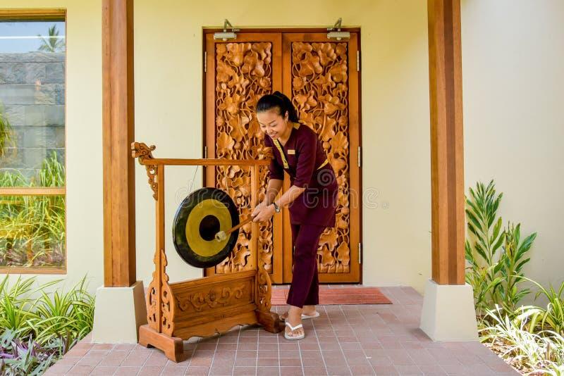 Thai restaurant waitress using the gong stock image