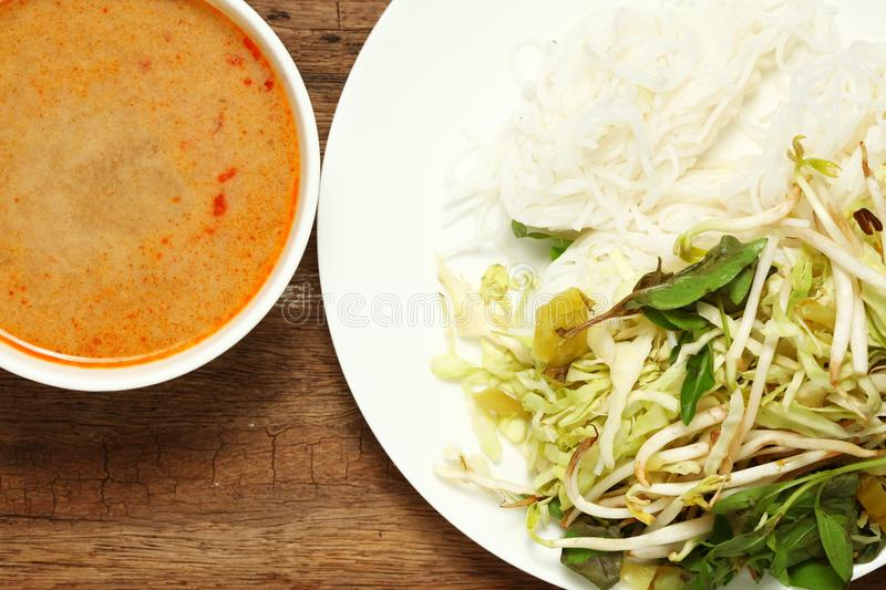 Thai food scene. Thai rice flour noodles put beside bean sprouts hoary basil leaf and mustard green with spicy sauce put in the white dish represent the thai royalty free stock image