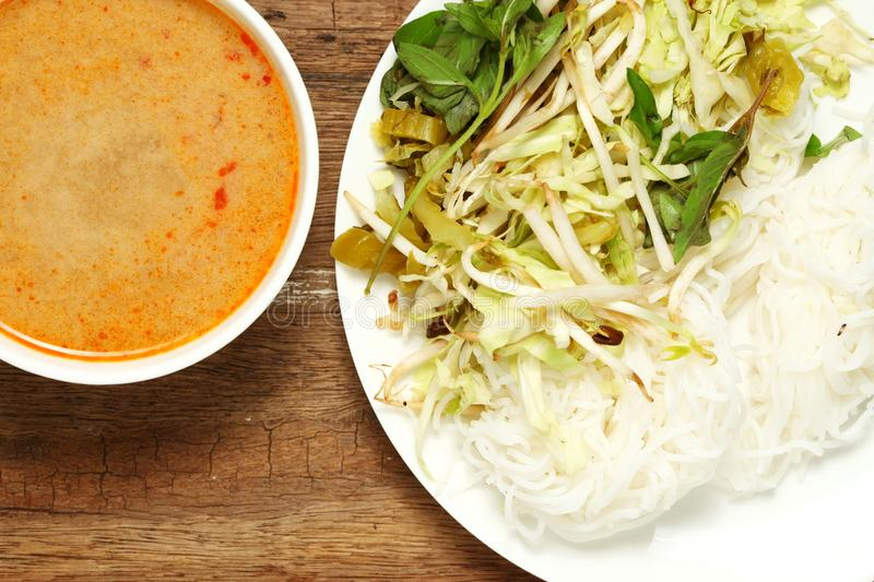 Thai food scene. Thai rice flour noodles put beside bean sprouts hoary basil leaf and mustard green with spicy sauce put in the white dish represent the thai royalty free stock images
