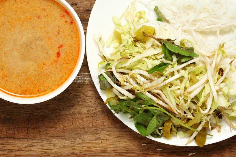 Thai food scene. Thai rice flour noodles put beside bean sprouts hoary basil leaf and mustard green with spicy sauce put in the white dish represent the thai royalty free stock photos