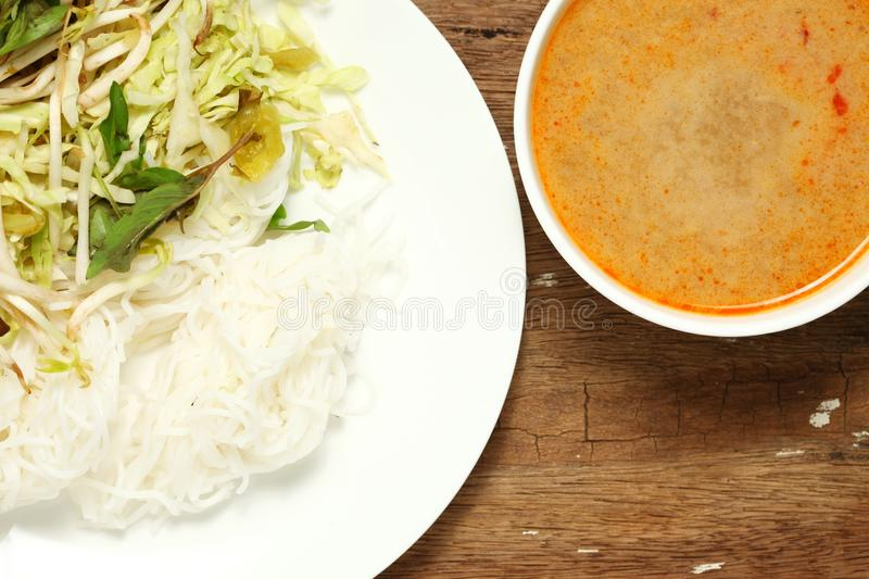 Thai food scene. Thai rice flour noodles put beside bean sprouts hoary basil leaf and mustard green with spicy sauce put in the white dish represent the thai stock photography