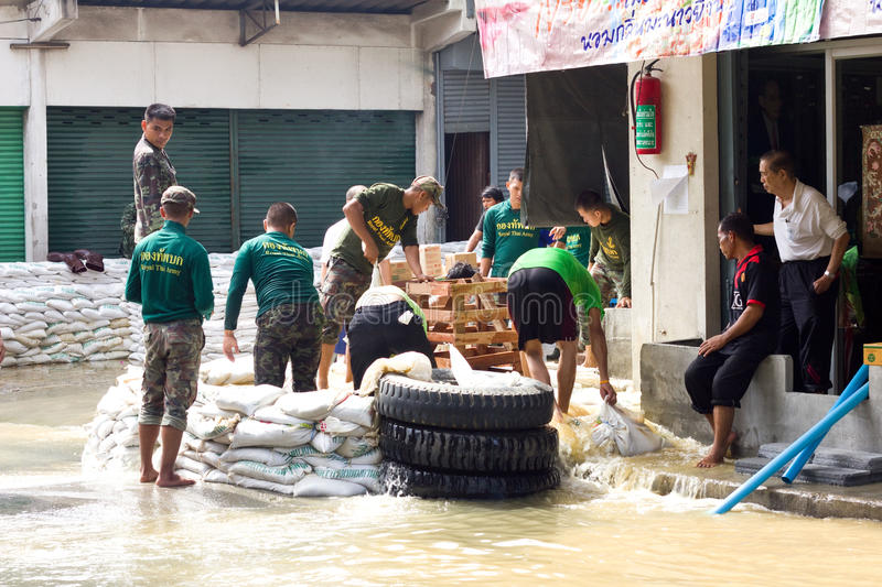 Thai soldiers are helping people. BANGKOK THAILAND - OCTOBER 28 : Thai soldiers are helping people who have suffered from flooding. on October 28, 2011 in stock photo