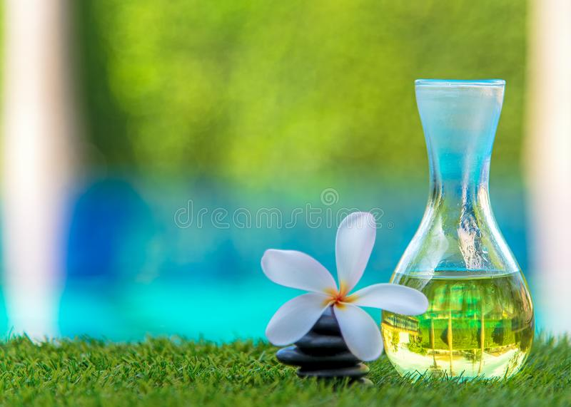 Thai Spa massage with rock spa and aroma oil with Plumeria flowers near swimming pool. Thailand, soft and select focus stock photography