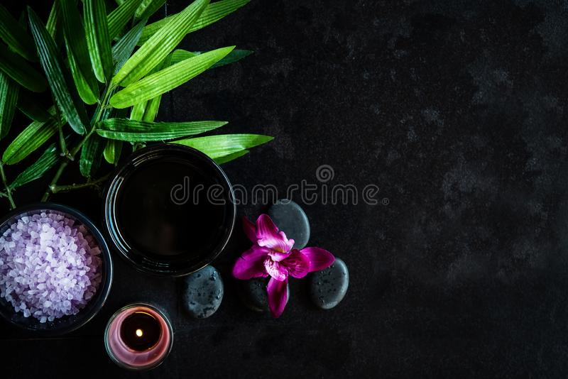Thai Spa.  Top view of hot stones setting for massage treatment and relax with purple orchid on blackboard with copy space. Green leaf with black stones pile royalty free stock photos