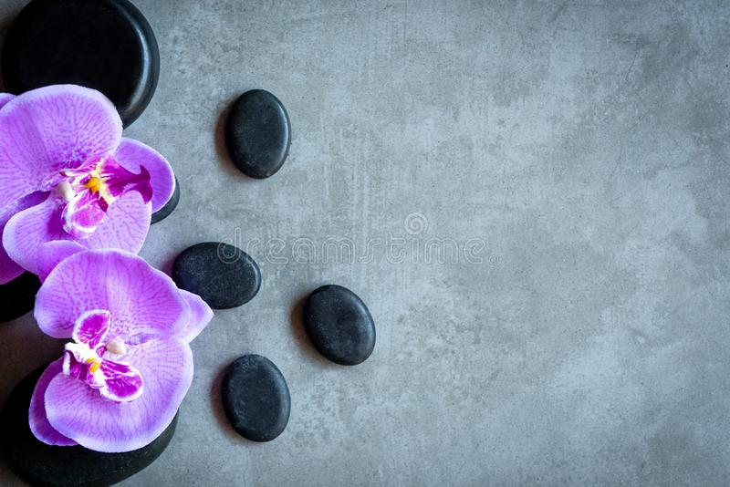 Thai Spa. Top view of hot stones setting for massage treatment and relax with purple orchid on blackboard with copy space. Lifestyle and Healthy Concept stock images