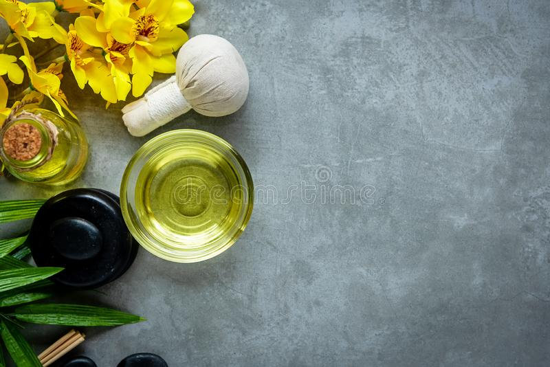 Thai Spa. Top view of hot stones setting for massage treatment and relax with yellow orchid on blackboard with copy space. Green leaf with black stones pile stock photography