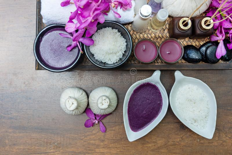 Thai Spa Treatments aroma therapy salt and nature sugar scrub and rock massage with orchid flower on wooden with candle. Thailand. stock photo