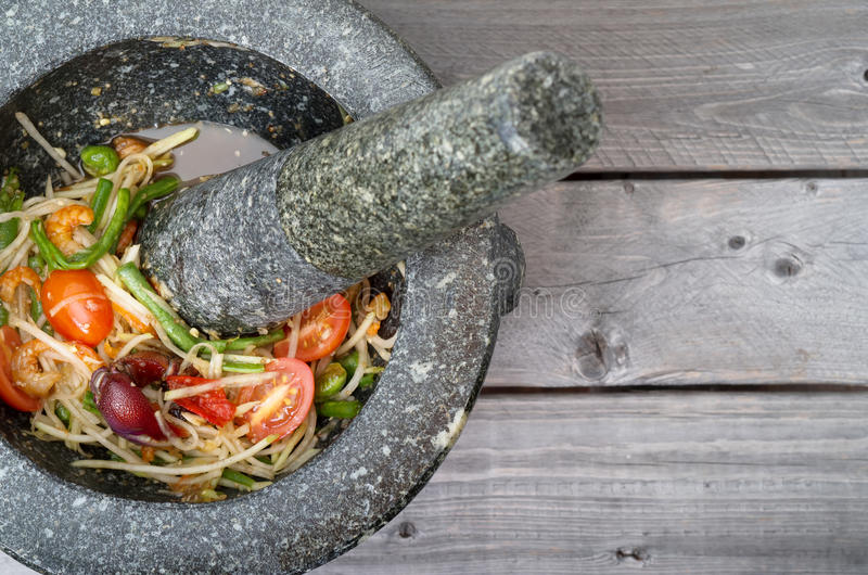 Thai spicy green papaya salad. In traditional marble mortar and pestle on wooden table royalty free stock photos