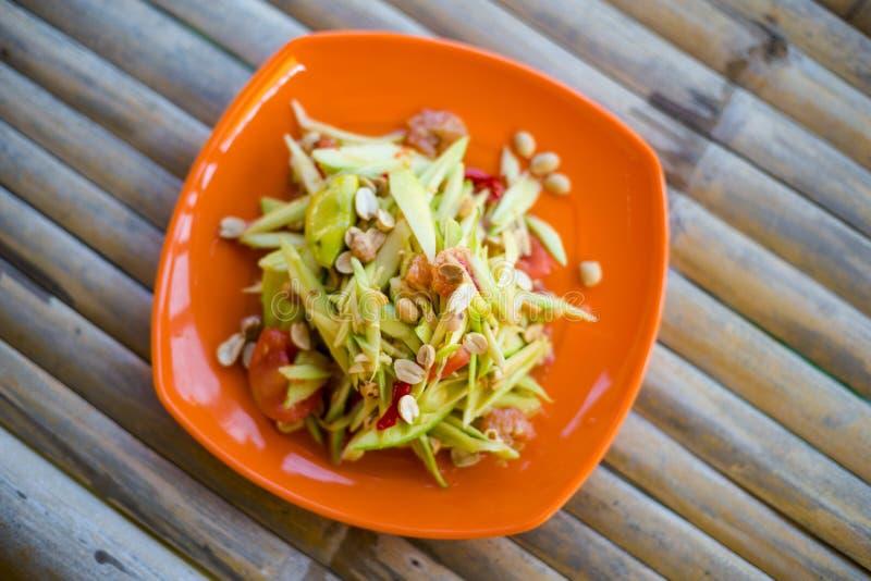 Thai spicy mango salad Lanta. Fresh prepared asian spicy mango Som Tam style salad in local restaurant on Koh Lanta island. Traditional thai cuisine made of royalty free stock images