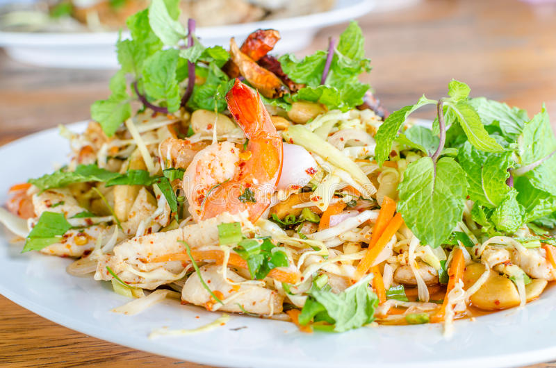 Thai Spicy salad with chicken, shrimp, fish and vegetables royalty free stock image