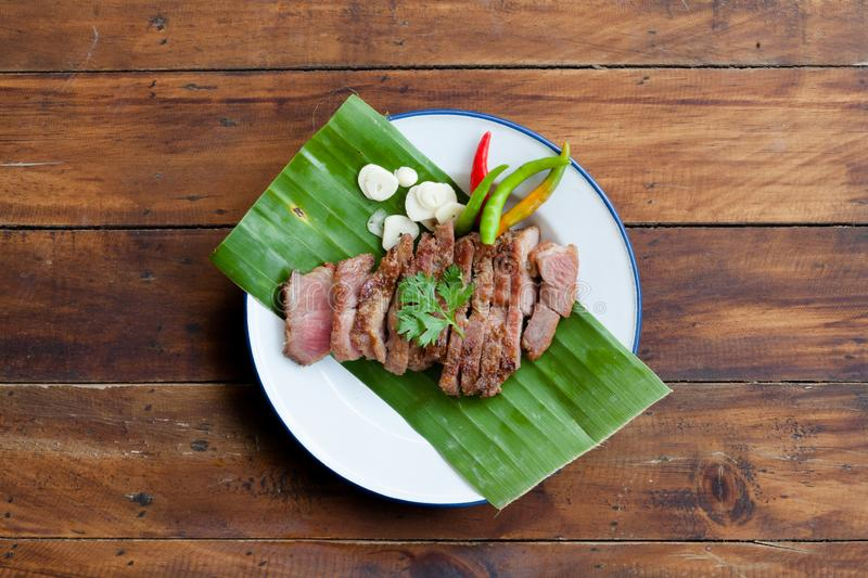 Thai street food Kor moo yang or charcoal grilled pork neck. On white plate and wood table background royalty free stock photography