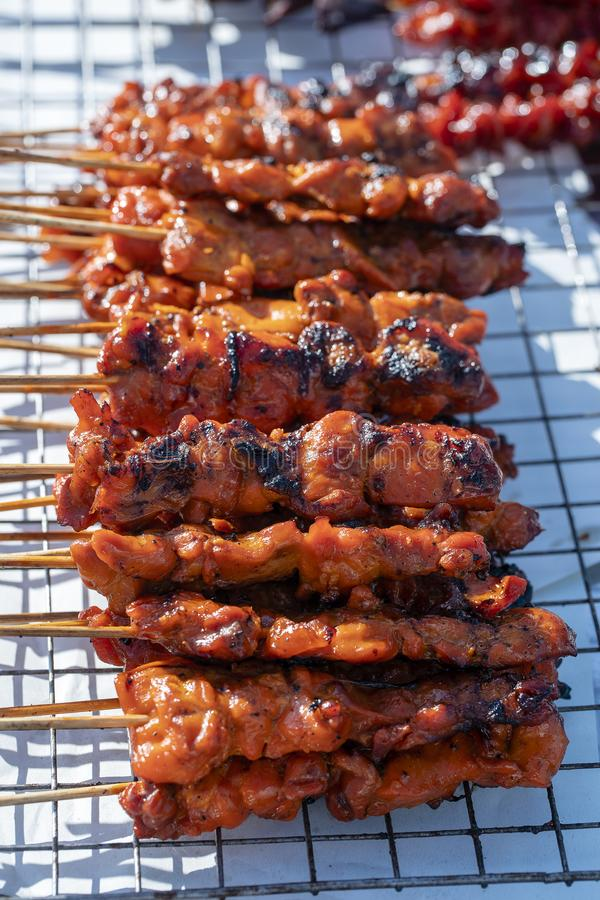 Thai street vendor sells grilled chicken meat at street food market in island Koh Phangan, Thailand. Closeup. Thai street vendor sells grilled chicken meat at royalty free stock photo