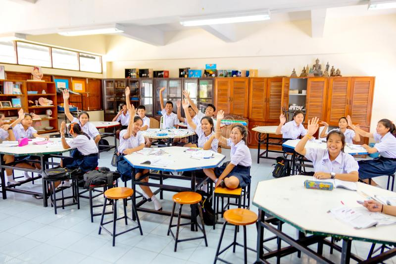 Thai students raise their hand to vothe for something in classroom at Praknampran, Thailand August 20, 2017 royalty free stock image
