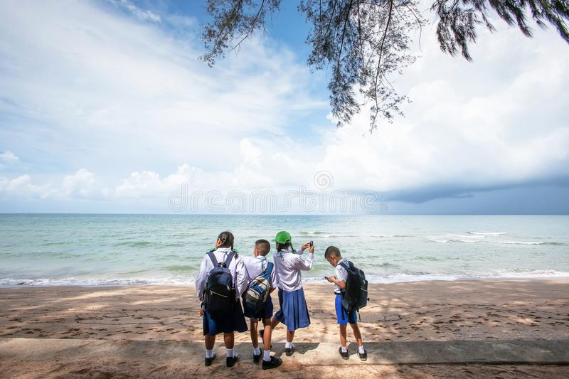 Thai students relaxing at seaside during on a field trip royalty free stock photography