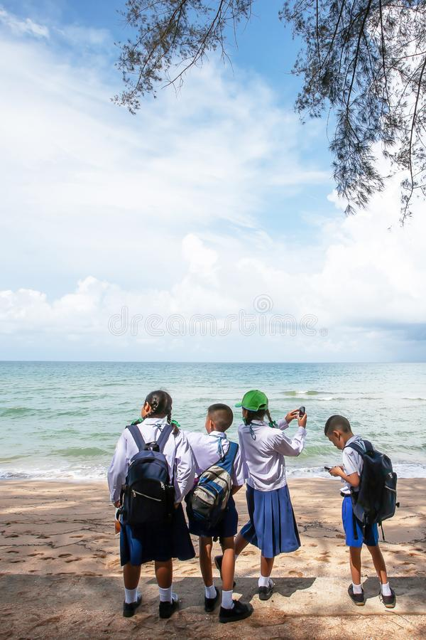 Thai students relaxing at seaside during on a field trip stock images