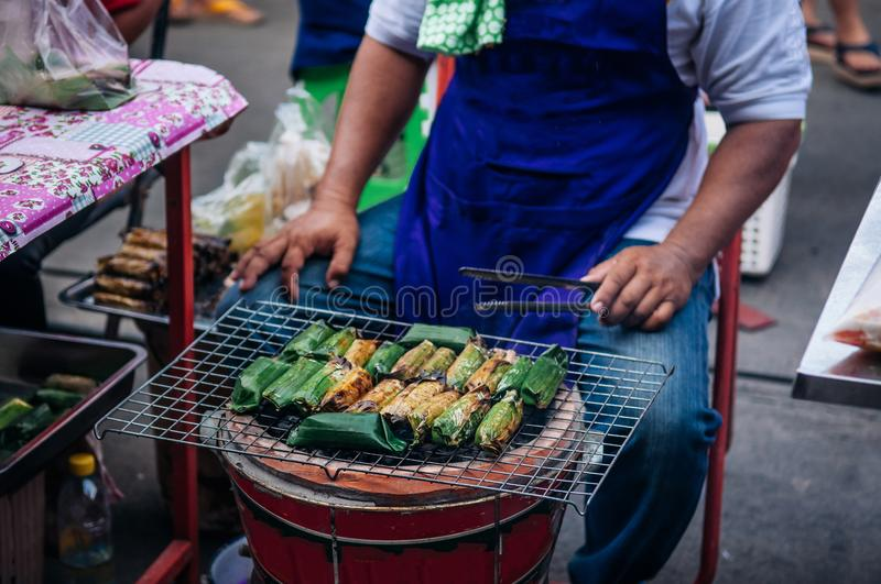 Thai style charcoal grill sticky rice dessert in banana leaf at. Thai style charcoal grill sticky rice dessert wrapped in banana leaf at local market in Uthai royalty free stock photography