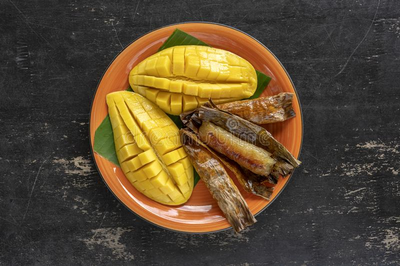 Thai style dessert, yellow mango with banana sticky rice in palm leaves. Yellow mango and sticky rice is popular traditional food royalty free stock photos