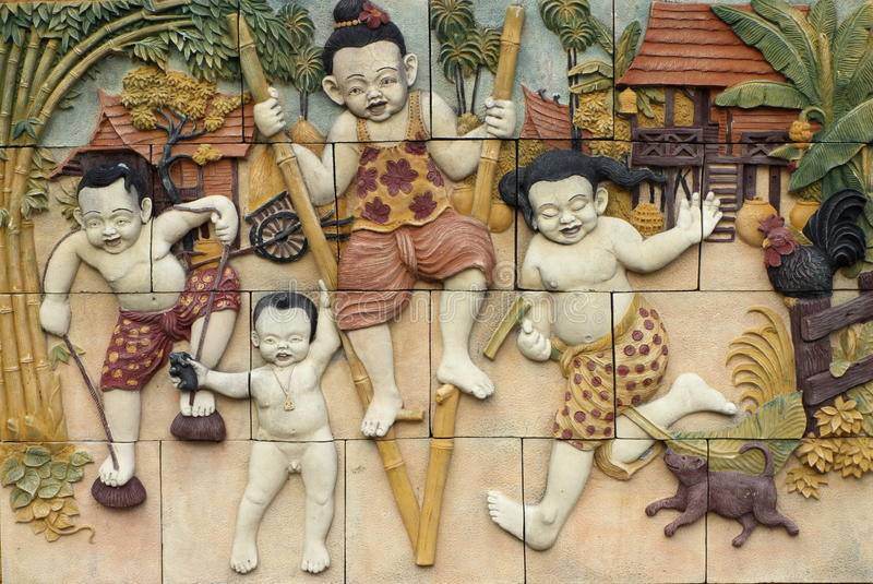 Thai style handcraft games of Thailand culture on wall. Low relief cement Thai style handcraft games of Thailand culture on wall, artwork for decor royalty free stock image