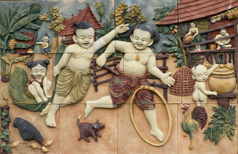 Thai style handcraft games of Thailand culture on wall. Low relief cement Thai style handcraft games of Thailand culture on wall, artwork for decor stock images