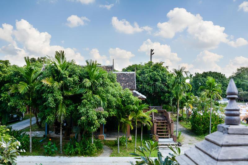 Thai style house located among many green trees royalty free stock photo