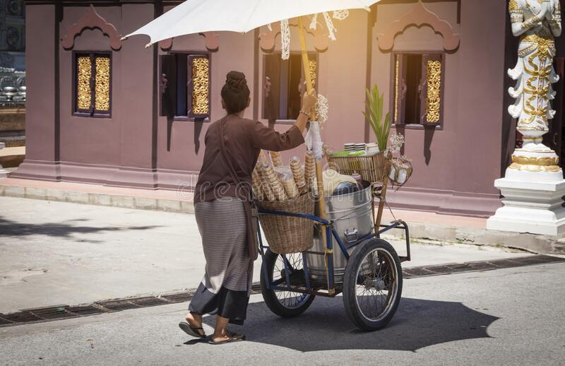 Thai style Ice cream cart and asian women with white fabric umbrella stock photography