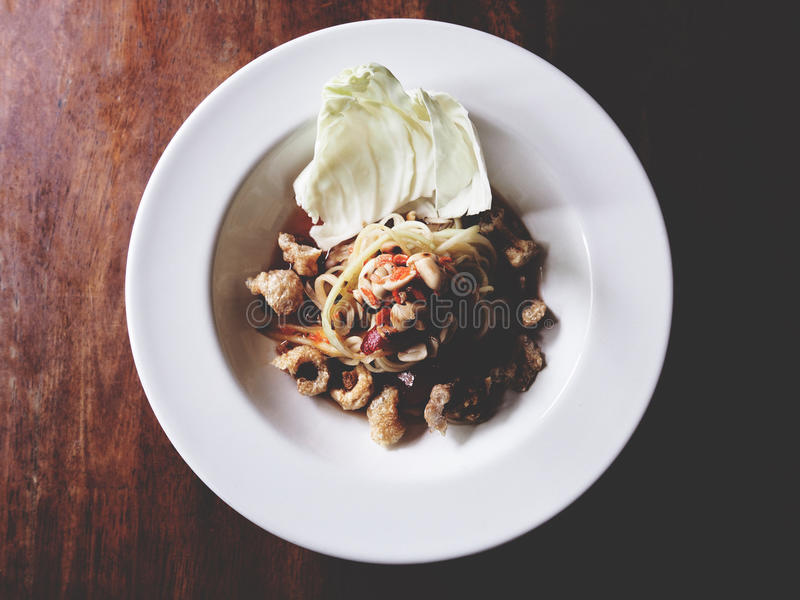 This is Thai style papaya salad with pork crackling on white plate above wooden, soft tone stock images