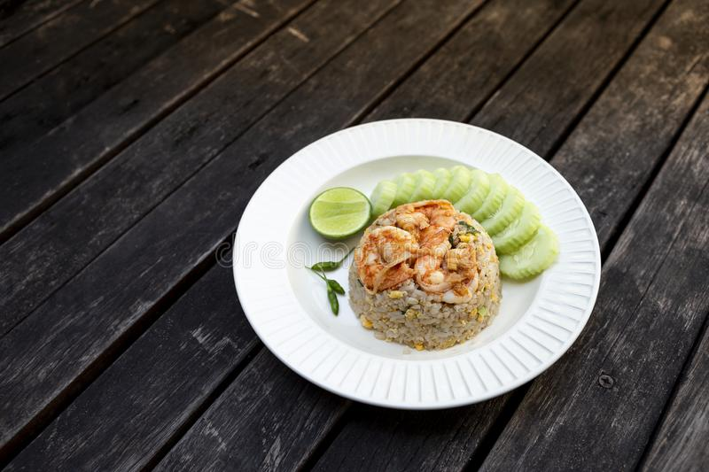 Thai style shrimps fried rice with fresh cucumber and lime on white ceramic plate stock images