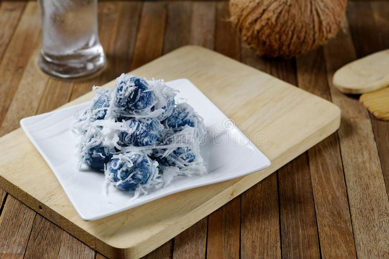 Thai sweet Coconut munchkins, Boiled Sticky Rice Flour with caramelized coconut filling,Violet colour from Butterfly pea.  royalty free stock photo
