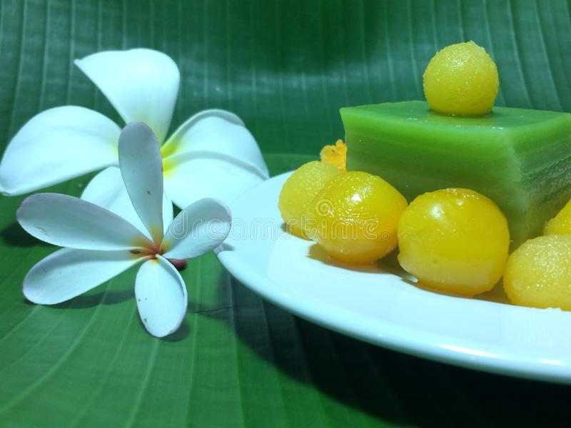 Closed up image of Thai sweet desert, traditional food in Thailand. Thai sweet desert decorating on white ceramic plate the background is green fresh banana royalty free stock photo