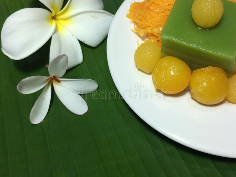 Closed up image of Thai sweet desert, traditional food in Thailand. Thai sweet desert decorating on white ceramic plate the background is green fresh banana stock photography
