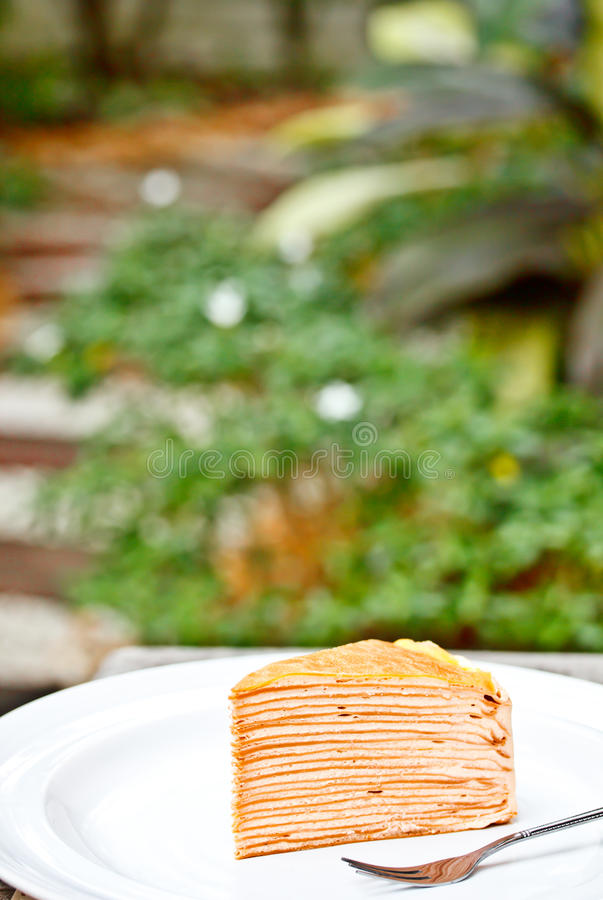Thai tea crepe cake in garden. Crepe cake on white dish with a steel fork in garden royalty free stock images