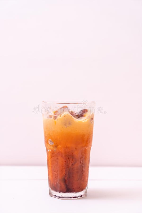 Thai tea ice cube with milk. On wood background royalty free stock photography