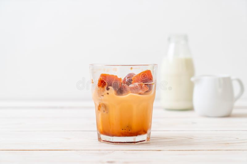 Thai tea ice cube with milk. On wood background stock photo