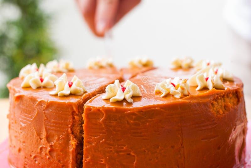 Thai tea layer cake. Cutting the thai tea layer cake on the table stock images