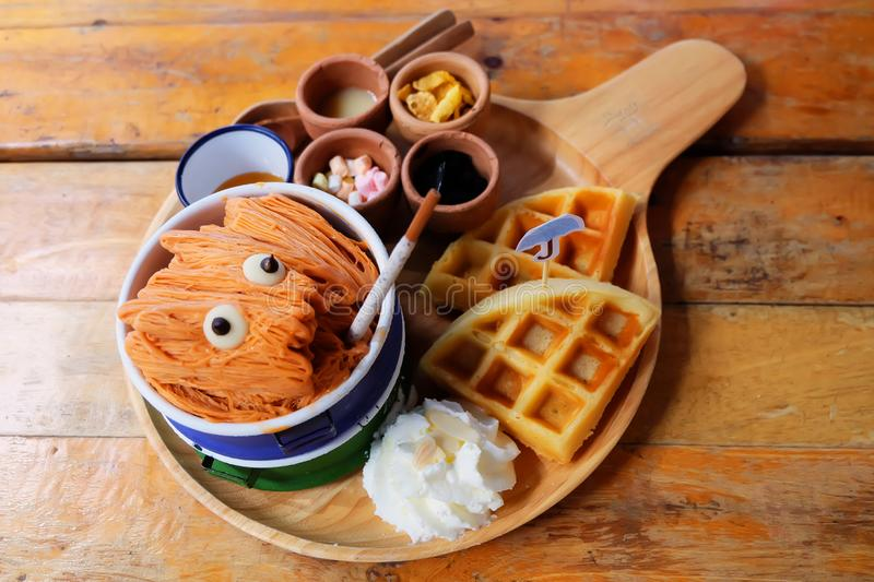 Thai Tea Shaved Ice. Milk Tea Shaved Ice Dessert with Bread and Topping Whipping Cream On Wooden Table Background royalty free stock image