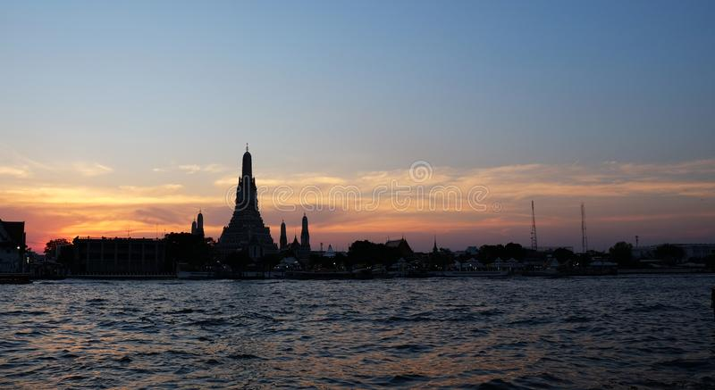 Thai temple Wat Arun stands on the banks of the Chao Phraya river at sunset. Evening landscape stock image