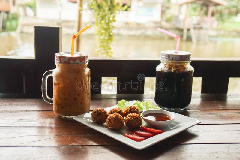 Thai traditional fried pork ball with noodles and iced beverages in vintage cafe along river royalty free stock photography