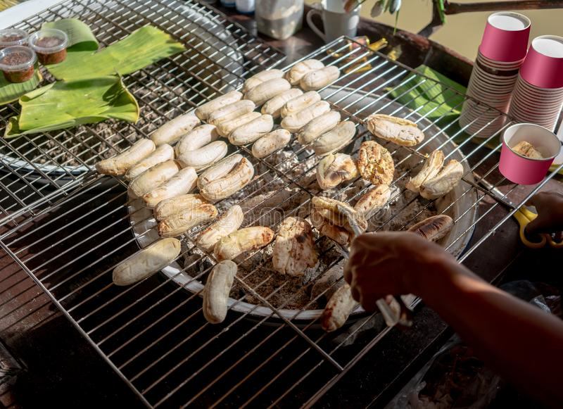 Thai traditional grilled banana on metal mesh over fire charcoal stock photography