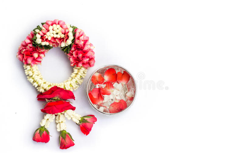 Thai traditional jasmine garland and water in bowl with jasmine and rose petals royalty free stock photo