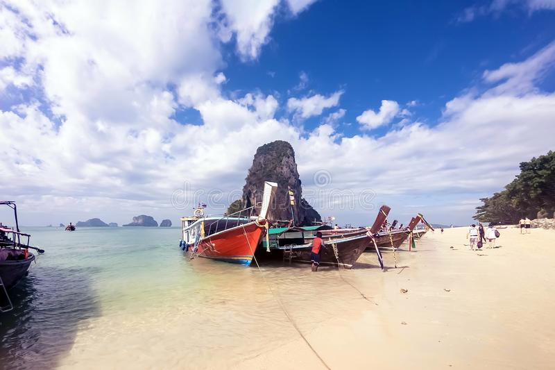Thai traditional wooden longtail boat and beautiful sandy beach in Krabi province. Cave mountain at background. Cloudy blue sky stock images