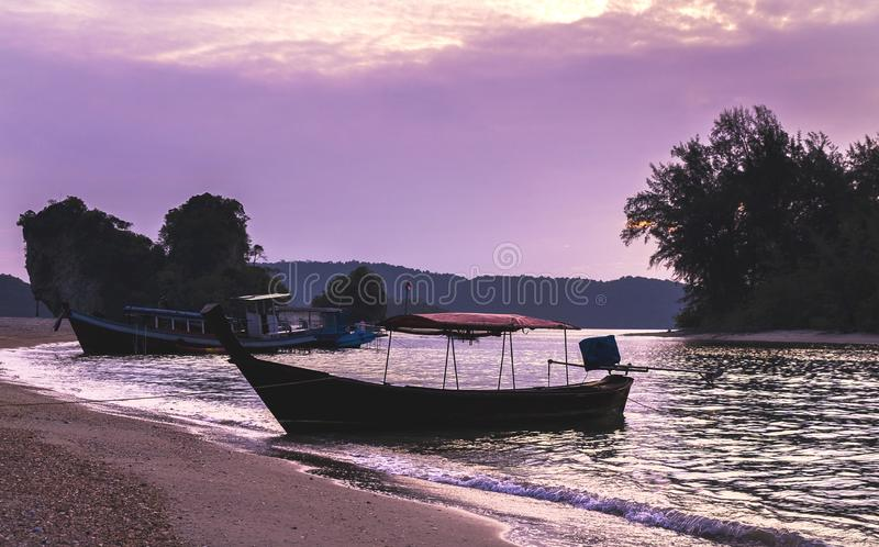 Thai traditional wooden longtail boats at the purple sunset in Krabi province. Thailand. stock image